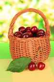 Cherry berries in wicker basket on table on bright background — Stock Photo