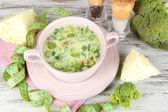 Cabbage soup in plate on napkin on wooden table — Stock Photo