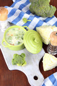 Cabbage soup in plate on board for cutting near napkin on wooden table — Stock Photo