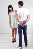 красивая влюбленная пара с цветами на сером фоне — Стоковое фото