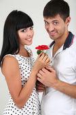 Mooie verliefde paar met rose op grijze achtergrond — Stockfoto