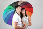 Beautiful loving couple with umbrella on grey background — Stock Photo
