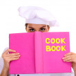 Portrait of young woman chef with cook book isolated on white — Stock Photo