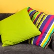 Colorful pillows on couch on yellow background — Stock Photo #26936631