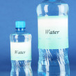 Different water bottles with label on blue background — Stock Photo