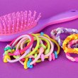 Scrunchies, hairbrush and hair - clip on pink background — Stock Photo #26938387