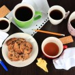 Stock Photo: Cups of coffee and cookies on plate on dark background