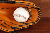 Baseball glove and ball on wooden background — Стоковое фото
