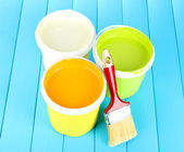 Set for painting: paint pots, brushes on blue wooden table — Stock Photo