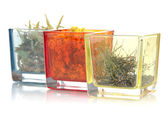 Dried herbs in glass containers isolated on white — Stock Photo