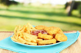 Fried chicken nuggets with french fries and sauce on table in park — Stock Photo