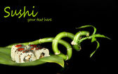 Tasty sushi on green leaf on dark background — Stock Photo