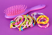 Scrunchies, hairbrush and hair - clip on a pink background — Stock Photo