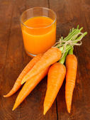 Heap of carrots, glass of juice, on wooden background — Stock Photo