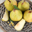 Stock Photo: Pears on braided tray on wooden table