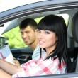 Beautiful young woman taking driving lesson — Stock Photo