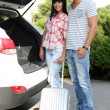 Portrait of happy beautiful couple putting suitcase into car — 图库照片