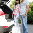 Portrait of happy beautiful couple putting suitcase into car — Zdjęcie stockowe