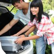 Portrait of happy beautiful couple putting suitcase into car — ストック写真
