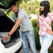 Portrait of happy beautiful couple putting suitcase into car — Foto de Stock