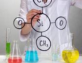 Kemist kvinna skriva formler på glas på grå bakgrund — Stockfoto