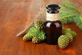 Bottle of fir tree oil and green cones on wooden background — Stock Photo