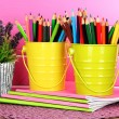 Colorful pencils in pails with copybooks on table on pink background — Foto Stock