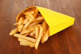 French fries in paper bag on wooden table close-up — Stock Photo