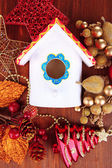 Nesting box and Christmas decorations on wooden background — Stock Photo