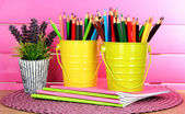 Colorful pencils in pails with copybooks on table on pink background — Stock Photo