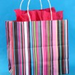 Striped shopping bag on blue background — Stock Photo