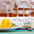 Table setting with glasses for different drinks on table on room background — Stock Photo #27095719