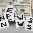 "White paper cubes labeled ""News"" with money on grey background — Foto Stock"