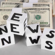 "Foto Stock: White paper cubes labeled ""News"" with money on grey background"