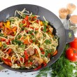 Stock Photo: Noodles with vegetables on wok isolated on white