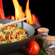 Stock Photo: Noodles with vegetables on wok on fire background
