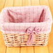 Stock Photo: Wicket basket with pink fabric and bow, on wooden background
