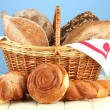 Composition with bread and rolls, in wicker basket on wooden table, on color background — Stock Photo