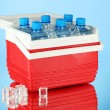 Traveling refrigerator with bottles of water and ice cubes, on blue background — Stock Photo