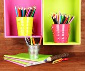 Färgglada pennor i hinkar på hyllorna på trä bakgrund — Stockfoto