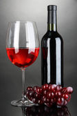 Red wine glass and bottle of wine on grey background — Stock Photo