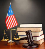 Wooden gavel, golden scales of justice and books on grey background — Stock Photo