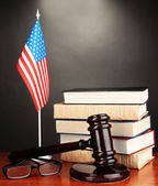 Wooden gavel, books and American flag on grey background — Stock Photo