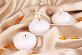 Candles on golden fabric close-up — Stock Photo