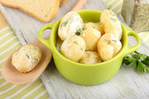 Tender young potatoes with sour cream and herbs in pan on wooden board on table close-up — Stock Photo