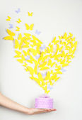Paper yellow butterfly in form of heart fly out box — Stock Photo