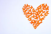 Paper butterflies in form of heart on wall — Stock Photo