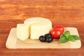 Sýr mozzarella, bazalka a zelenina na dřevěné pozadí — Stock fotografie