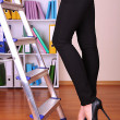 Woman climbing up ladder in office — Stock Photo