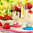 Delicious strawberry desserts in glass vase on wooden table on natural background — Stock Photo